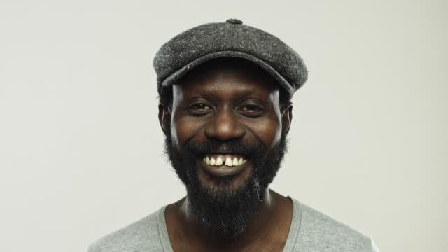 vidéos et rushes de afro américain mûr avec le sourire de barbe - fond gris