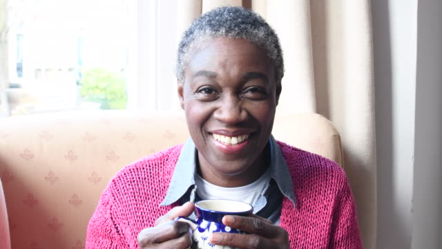 mature afro caribbean woman holding cup of coffee and smiling toward camera - coffee drink stock videos & royalty-free footage