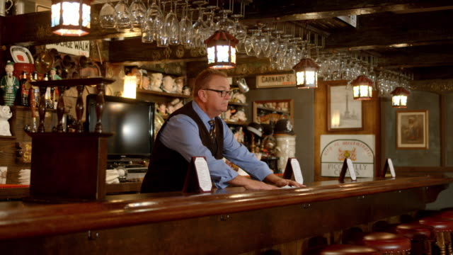 pan mature aged bartender placing drink napkins on bar counter in empty restaurant decorated in the style of traditional english country pub - napkin stock videos & royalty-free footage