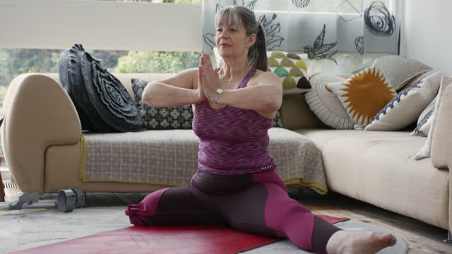 mature amputee mature woman in leotard meditating in sitting room - serene people stock videos & royalty-free footage