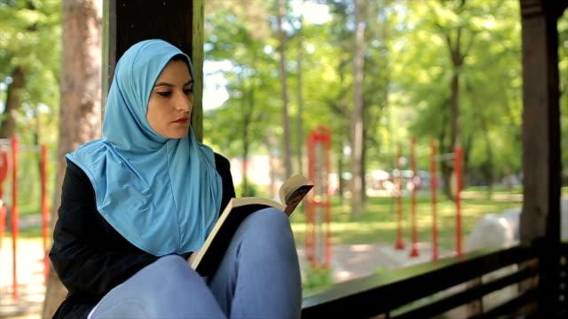 vídeos de stock, filmes e b-roll de mature árabe mulher lendo um livro ao ar livre, relaxamento e tempo livre - vestuário modesto