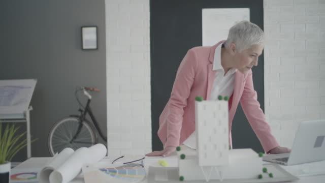 vídeos de stock e filmes b-roll de 4 k : madura arquiteto trabalhando em seu escritório. - cabelo branco