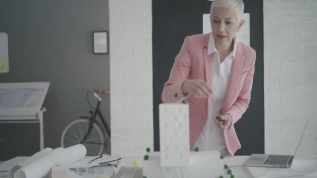 vídeos de stock e filmes b-roll de 4 k : madura arquiteto trabalhando em seu escritório. - arquiteta