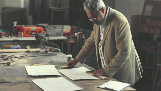 mature architect working on new project and analyzing blueprints in a workshop. - architetto video stock e b–roll