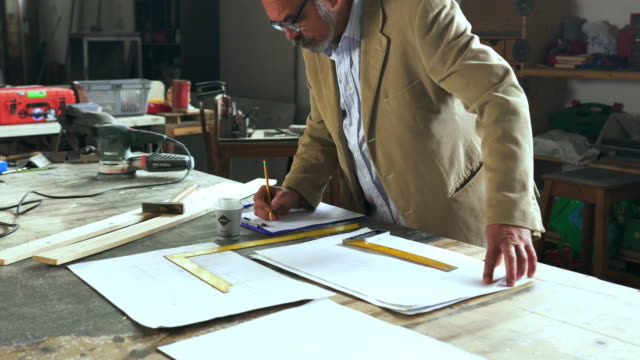 mature architect working on  new project plans at his workshop. - disegno video stock e b–roll