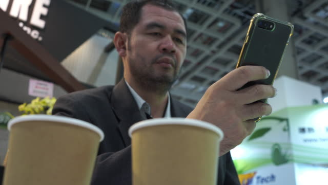 mature asian businessman using phone in office exhibition and drink hot coffee with take away cup - coffee drink stock videos & royalty-free footage
