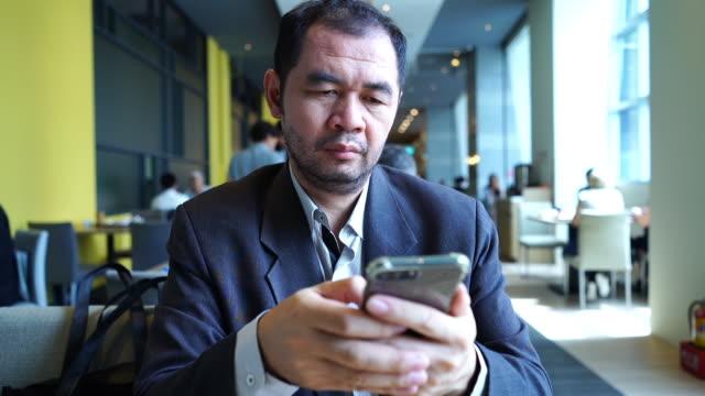 成熟的亞洲商人在餐廳使用手機 - 僅一成熟男士 個影片檔及 b 捲影像