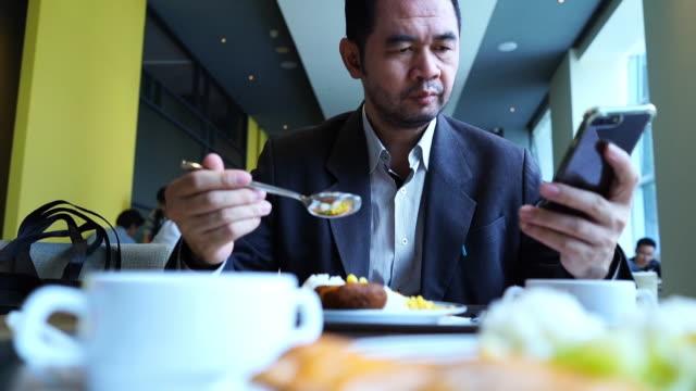 成熟的亞洲商人使用電話,而吃的食物 - 僅一成熟男士 個影片檔及 b 捲影像