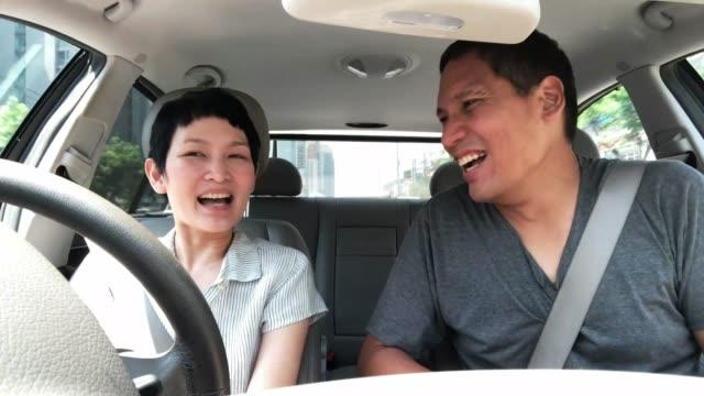 成熟したアジアのカップルが笑って車の中で面白い話をします。アジアの中年の友人は、運転中に良い会話を楽しみます - 中年点の映像素材/bロール