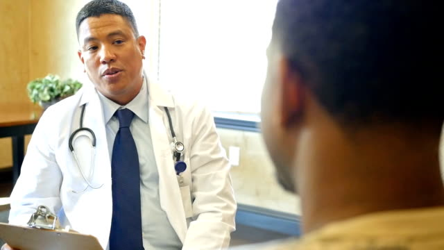 mature asian doctor talks with young african american male patient - patient stock videos & royalty-free footage