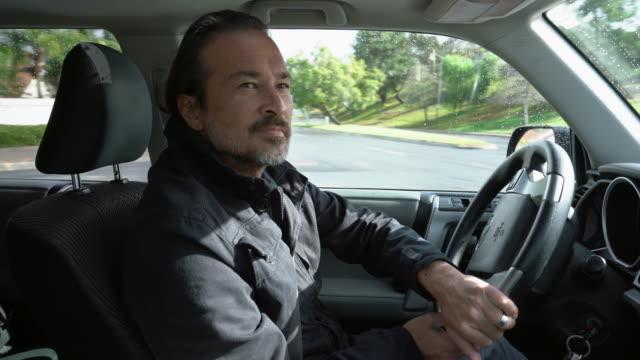 cu mature asian man driving a car - ユーラシアエスニシティ点の映像素材/bロール