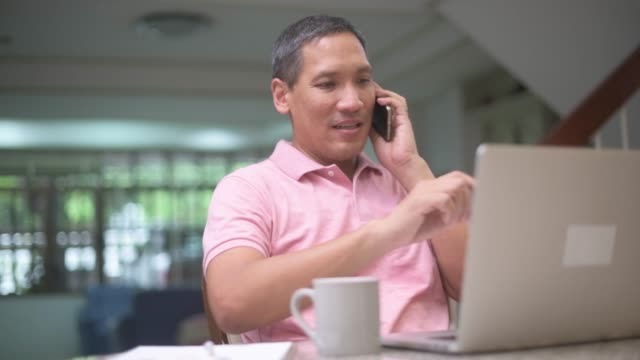 mature asian man talking on smart phone working from home with laptop and drink coffee, freelance and online business concept - mature adult stock videos & royalty-free footage