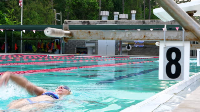 MS Mature athletes swimming during early morning workout in outdoor pool