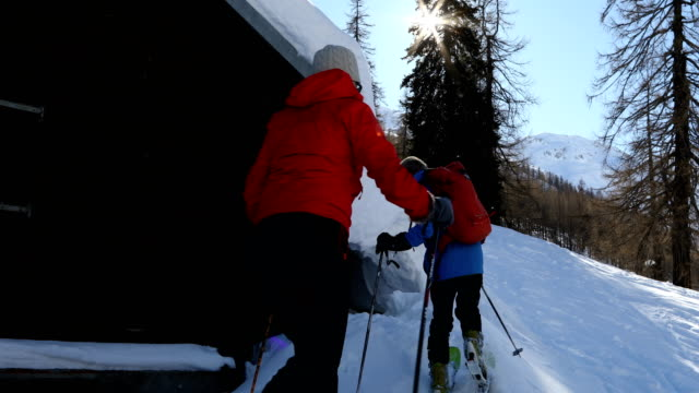 mature back-country skiing couple explore the swiss alps from mountain hut - mature couple stock videos & royalty-free footage