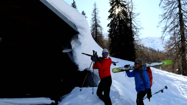 mature back-country skiing couple explore the swiss alps from mountain hut - hut stock videos & royalty-free footage