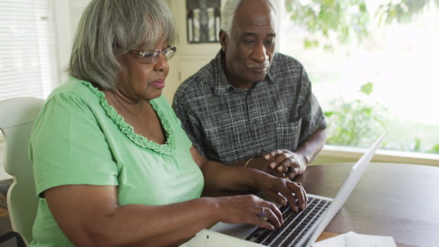 stockvideo's en b-roll-footage met mature black couple using laptop to do online banking - oudere internetgebruiker