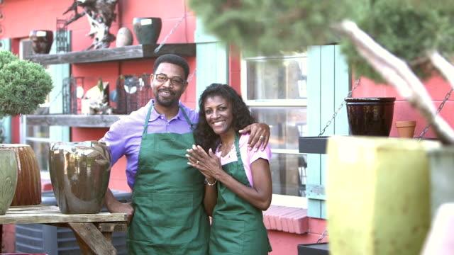mature black couple working in plant nursery - plant nursery stock videos & royalty-free footage