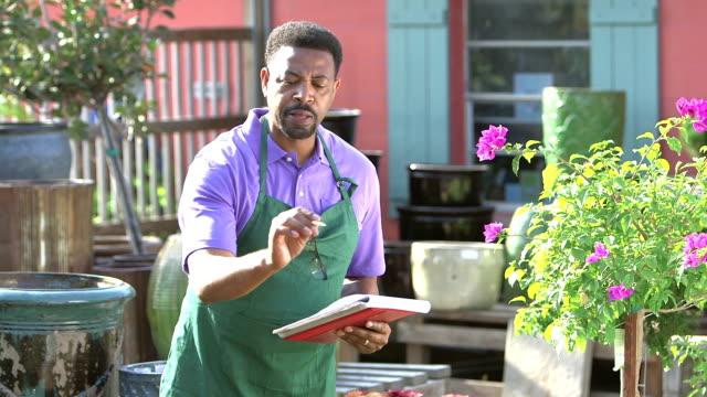 Mature black man in plant nursery taking inventory