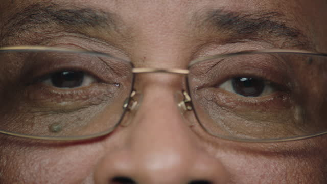 vídeos de stock e filmes b-roll de ecu slo mo. mature black man opens his eyes in slow motion. - olhos castanhos
