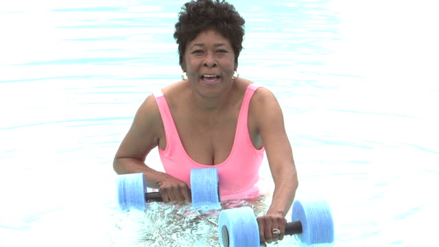 mature black woman doing water aerobics - aerobics stock videos & royalty-free footage