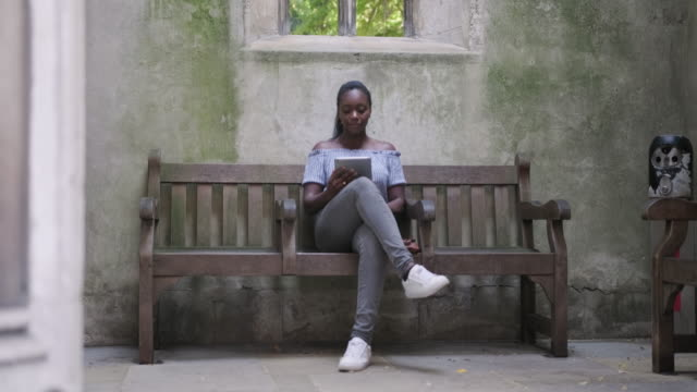 mature black woman sitting on a bench and using digital tablet to read a book in st dunstan in the east - attitude stock videos & royalty-free footage