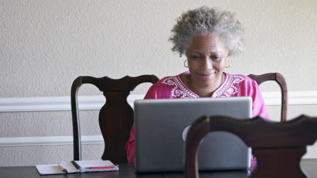 vídeos de stock e filmes b-roll de mature black woman using laptop in dining room - idoso na internet