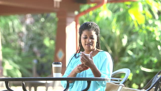 Mature black woman walks up to outdoor table with coffee