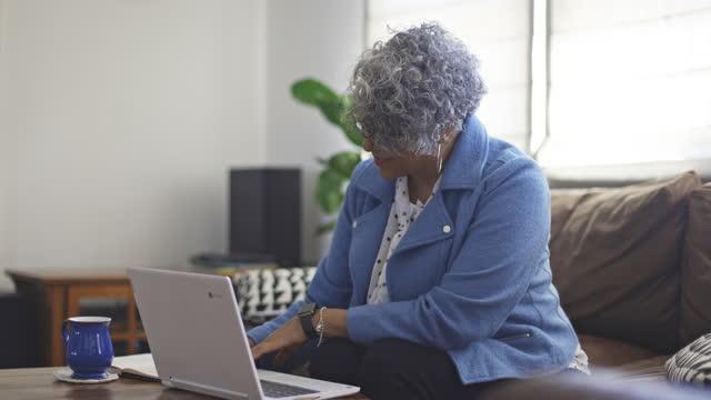 vídeos de stock e filmes b-roll de mature black woman working from home - sala de jantar