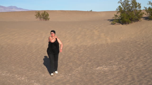 mature, body-positive happy woman hiking on sand dunes at mesquite flats, death valley, california. - body positive stock videos & royalty-free footage