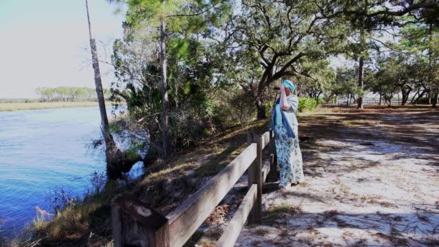 vídeos de stock, filmes e b-roll de pássaros de observação corpo-positivos maduros da mulher com binocular no parque estadual do rio de ochlockonee, florida norte - body positive