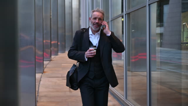 mature british businessman on the move and using smart phone - full suit stock videos & royalty-free footage