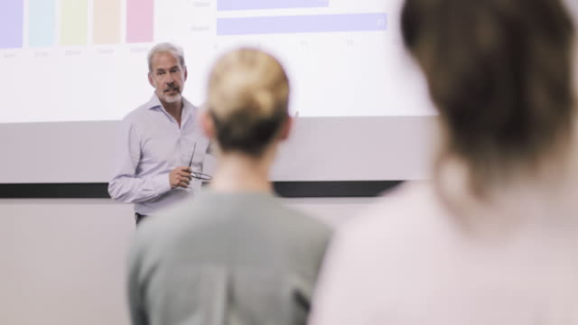 vídeos de stock e filmes b-roll de mature business executive giving a presentation - workshop