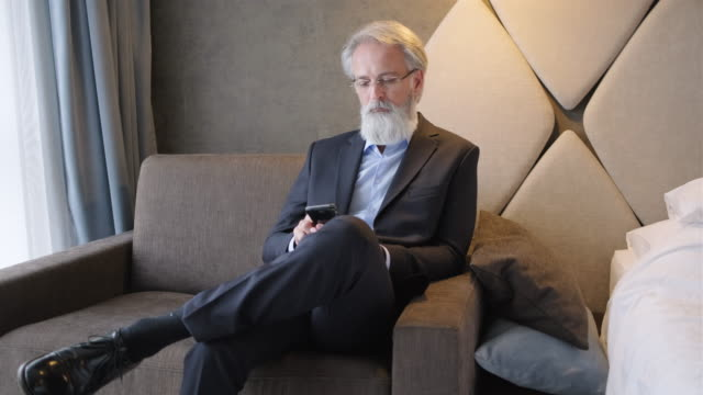 mature business executive using smart phone in hotel room - facial hair stock videos & royalty-free footage