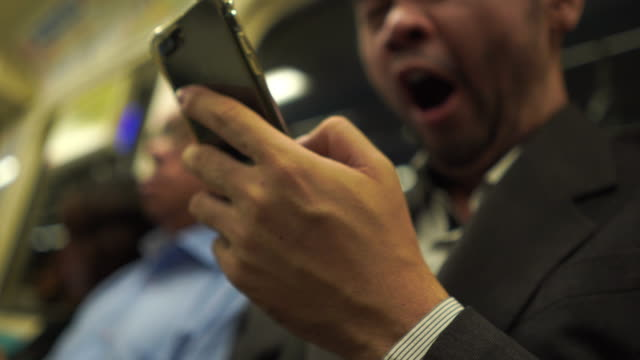 mature business man using smartphone on city train , yawning - overworked stock videos & royalty-free footage