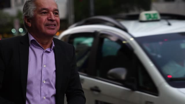 vídeos de stock, filmes e b-roll de maduras negócios homem esperando o taxi - táxi
