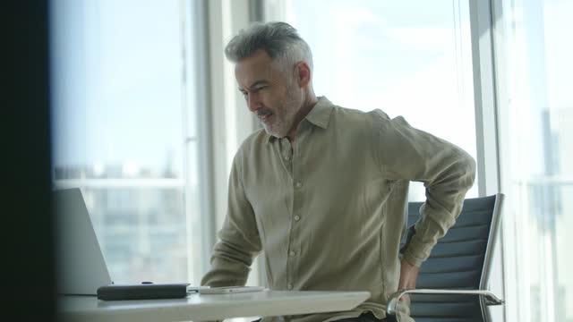 vídeos de stock, filmes e b-roll de homem de negócios maduro com segurando as costas em pai - cadeira de escritório
