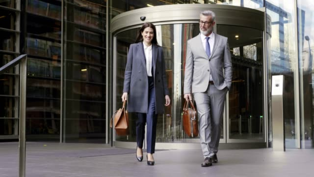 mature business people leaving office after work - building entrance stock videos & royalty-free footage