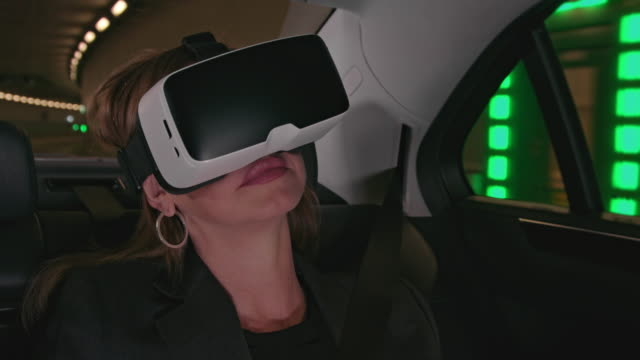 mature business woman in her forties with long brown hair gets chauffeured in a limousine through the city / driving with taxi through a tunnel while using a VR head set