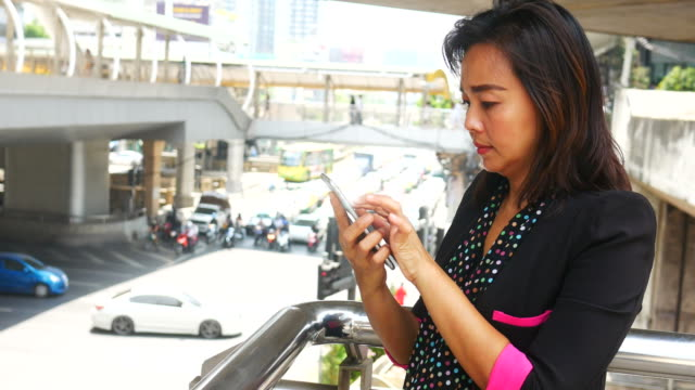 Mature business woman using a smart phone in urban backgrounds