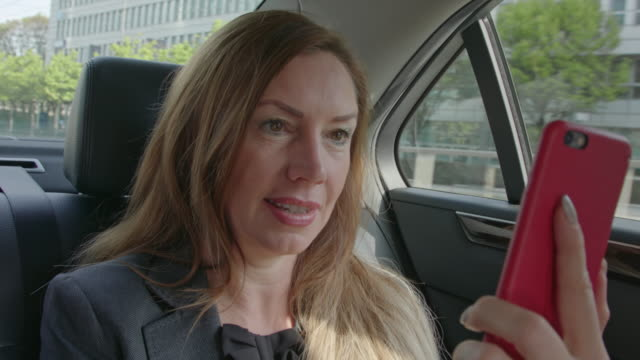 mature business woman with long brown hair gets chauffeured in a limousine through the city while having a conference video call with her mobile cell smart phone / driving taxi