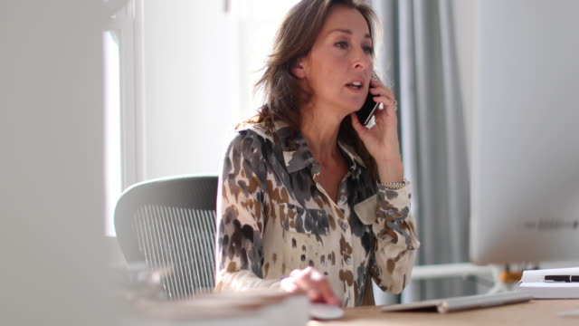 Mature business woman working on desktop computer and smartphone