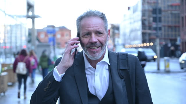 mature businessman approaching on sidewalk using smart phone - full suit stock videos & royalty-free footage
