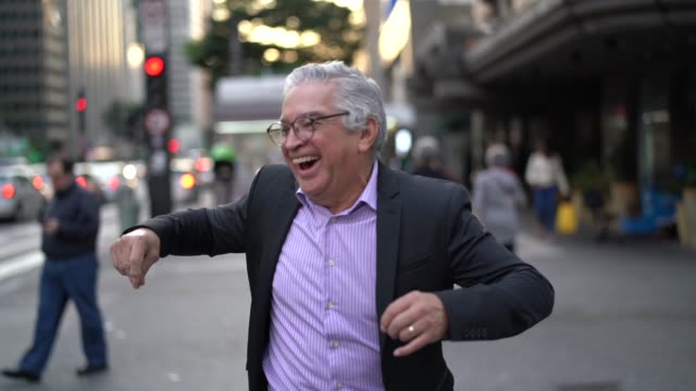 vídeos de stock e filmes b-roll de mature businessman dancing and having fun at street - ecstatic