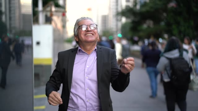 mature businessman dancing and having fun at street - attività del fine settimana video stock e b–roll