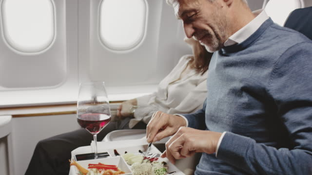 mature businessman eating lunch in private jet - aeroplane stock videos & royalty-free footage