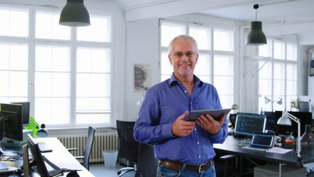 vídeos de stock e filmes b-roll de mature businessman holding a digital tablet in office - 50 54 anos