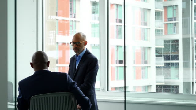 ms mature businessman in meeting with colleague in conference room - doing a favour stock videos & royalty-free footage