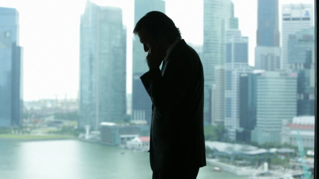 ws mature businessman in suit  looks out of window at city whilst using mobile phone - 窓越し点の映像素材/bロール