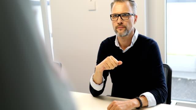 vídeos de stock e filmes b-roll de mature businessman listening to female colleague - 50 anos
