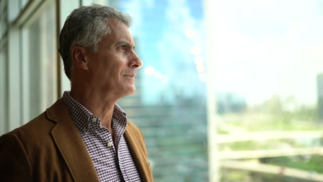 mature businessman looking out of window - hope stock videos & royalty-free footage